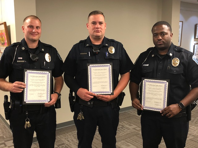 Officers after being sworn in, posing with certificates